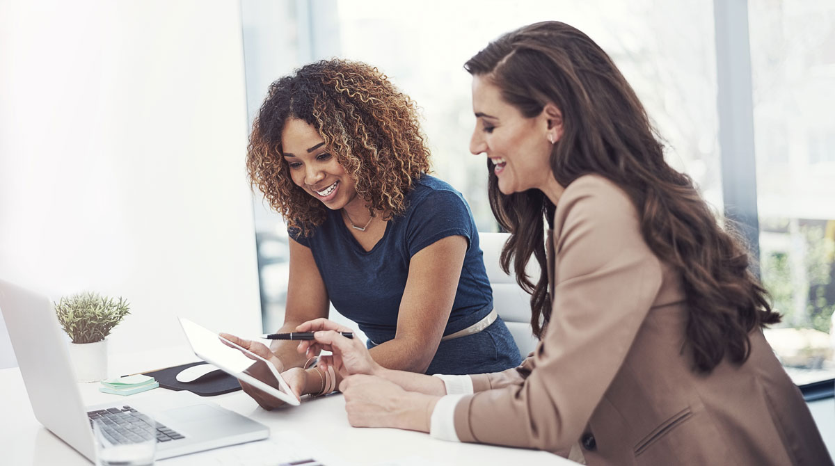 Two smiling women discussing benefits of cloud computing as shown on their tablet