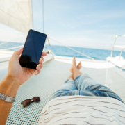 Image of a person on a yacht holding a cell phone
