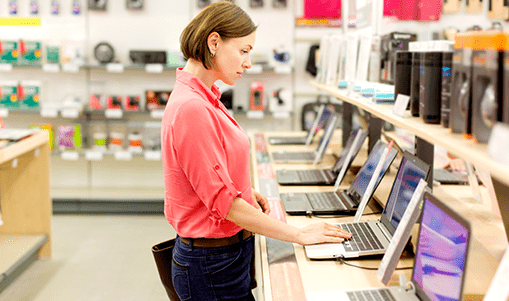 Woman in a computer retail shop tries out a laptop