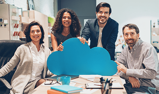 A smiling group at a desk holds onto a large cloud cutout illustrating cloud services