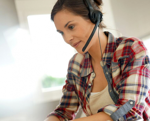 image of a woman with headphone working from btcc比特币数字货币交易所home
