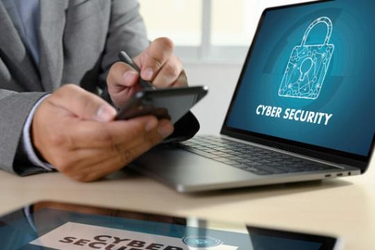 Man's hands hold a cell phone next to a laptop showing a padlock and the words Cyber Security