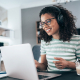 Young female call center agent answers customer inquiries on a laptop from home
