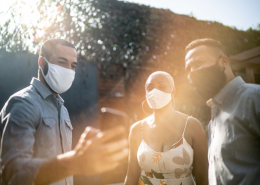 Image three people wearing masks and discussing COVID vaccine